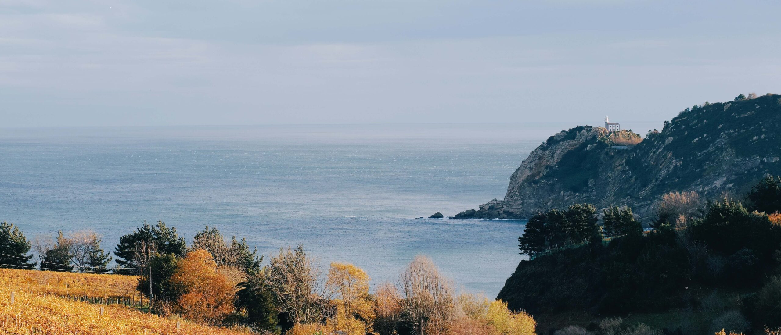 Distant lighthouse on an autumn morning seascape, in Getaria. Juan Sebastián Elcano's hometown, the first man to circumnavigate the earth.